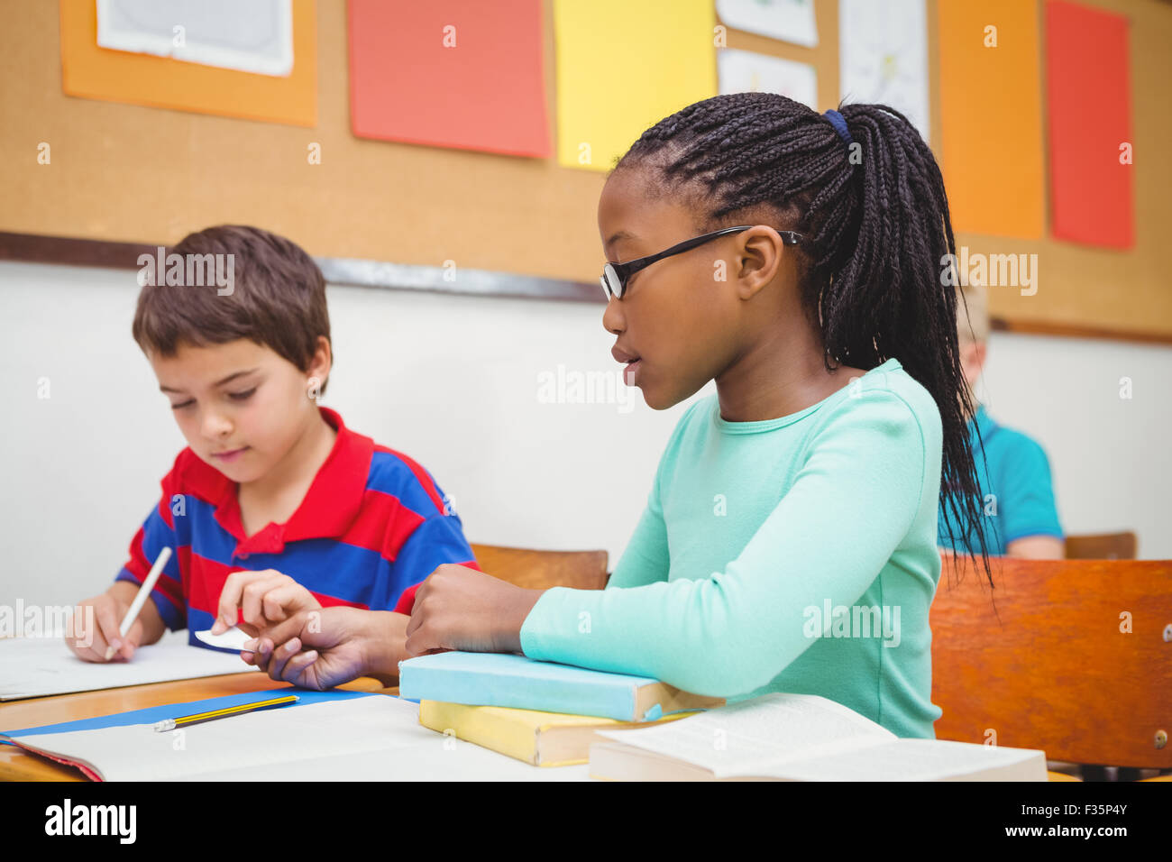 Student helping fellow student in class - Stock Image