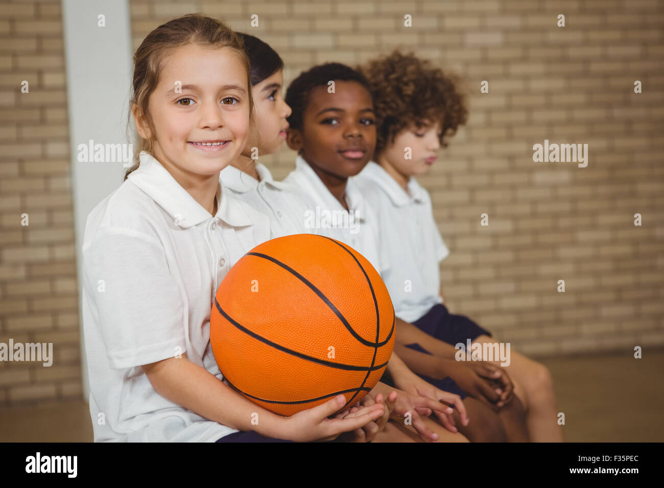 Student holding basketball with fellow players - Stock Image