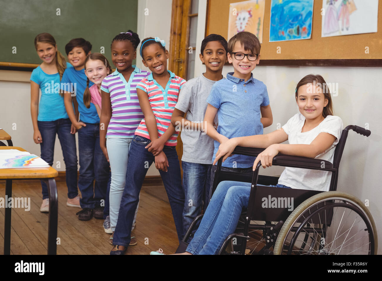 Disabled pupil smiling at camera with classmates - Stock Image