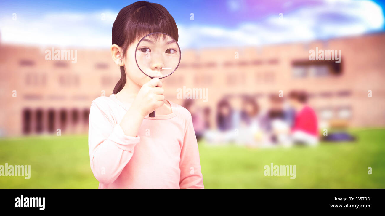 Composite image of pupil looking through magnifying glass - Stock Image