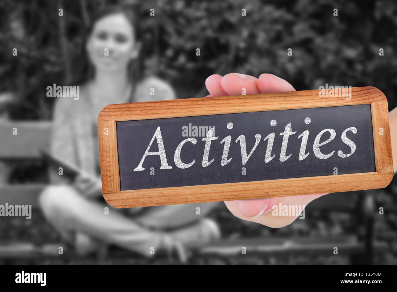 Activities against smiling student sitting on bench listening music with mobile phone and holding bo - Stock Image