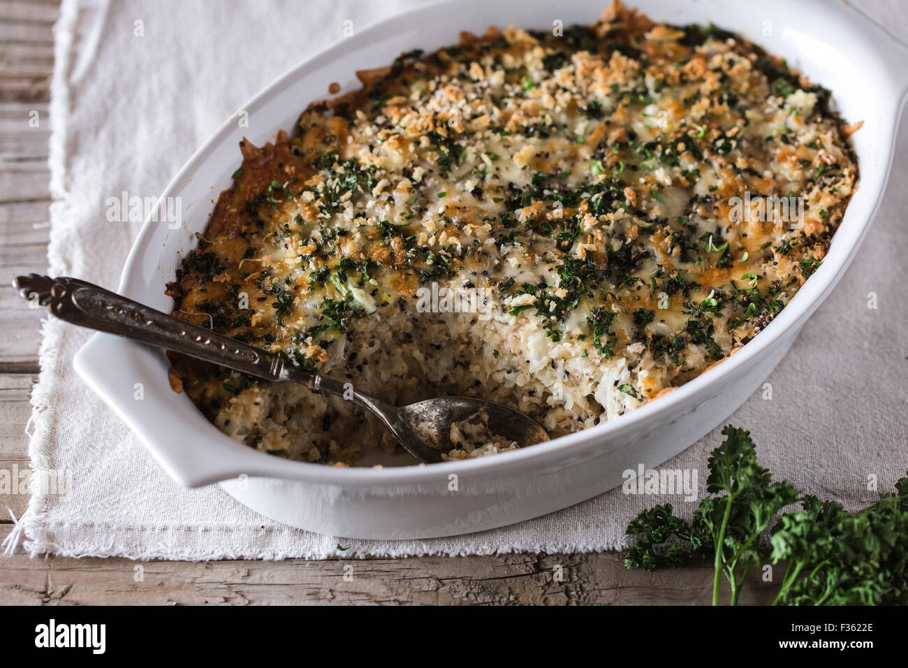 A Spicy Cauliflower Gratin with Crunchy Topping dish is displayed on a farm-style board and photographed from the - Stock Image