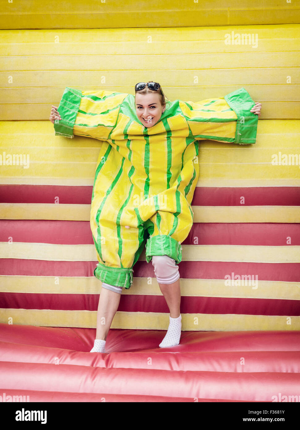 Young woman in plastic dress in a bouncy castle imitates a fly on velcro wall. Inflatable attraction. - Stock Image