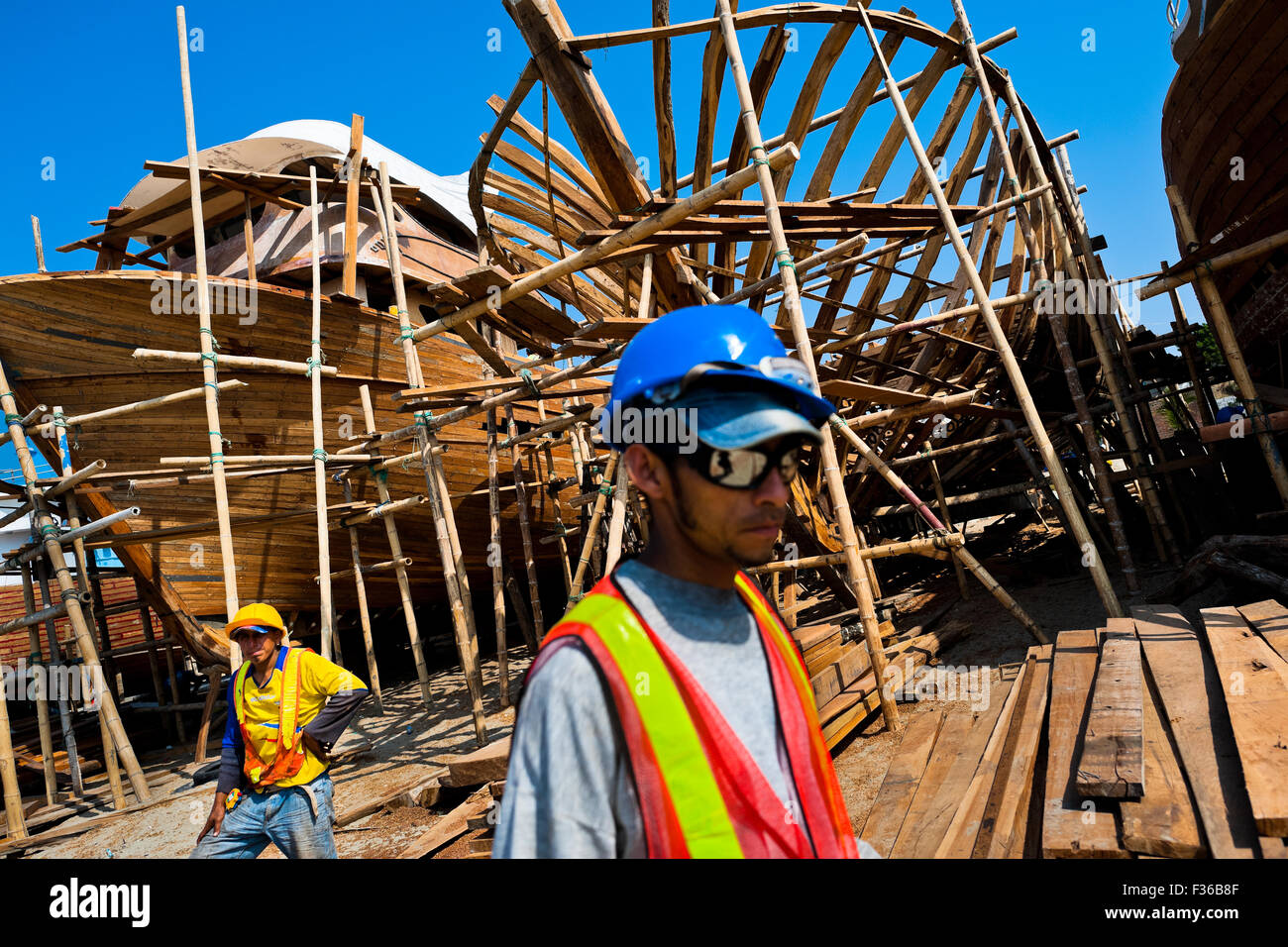 Ecuadorian shipbuilding workers build a traditional wooden fishing vessel in an artisanal shipyard in Manta, Ecuador. - Stock Image
