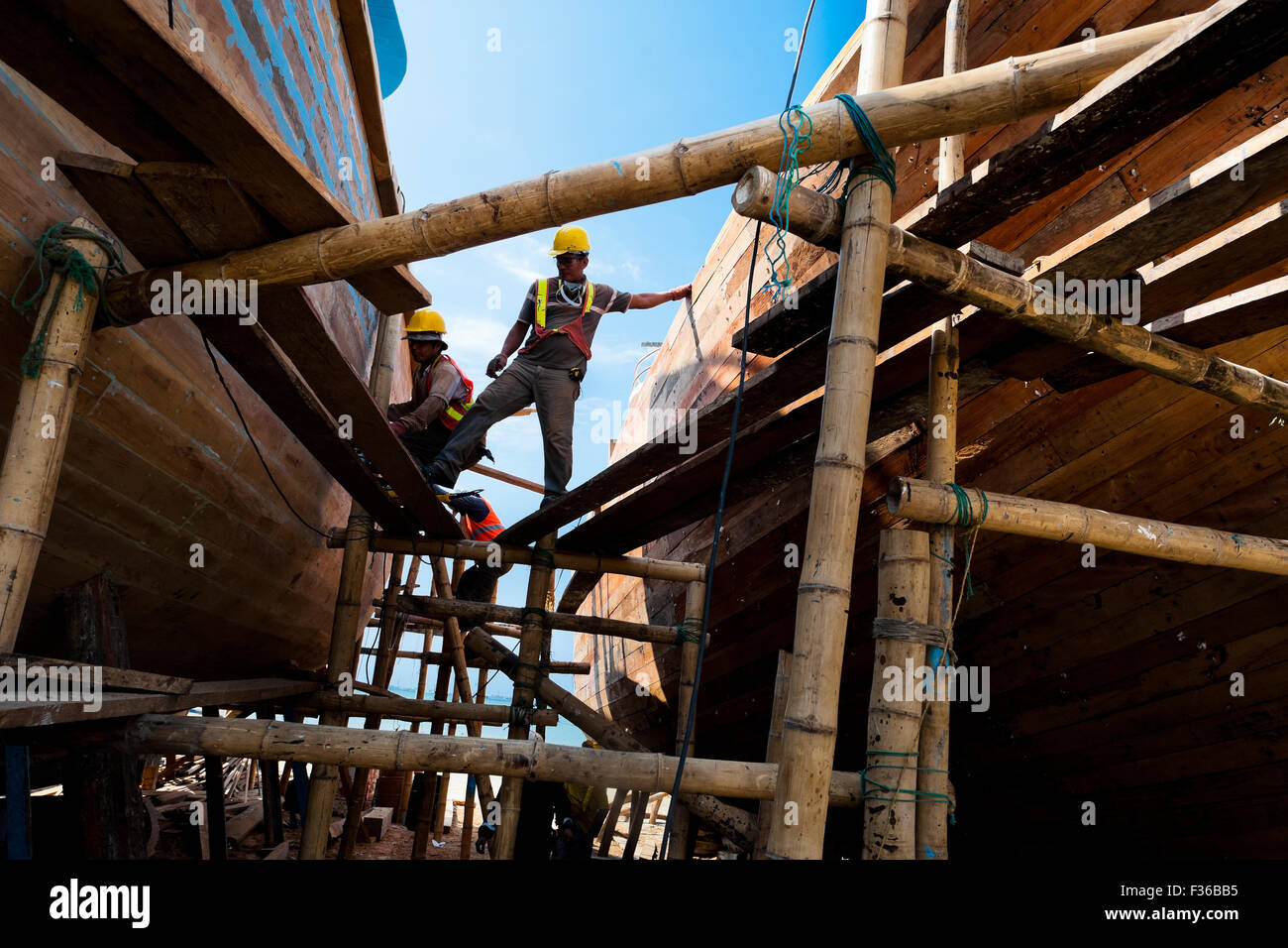 Ecuadorian shipbuilding workers provide maintenance to the traditional wooden fishing vessels in a shipyard in Manta, - Stock Image