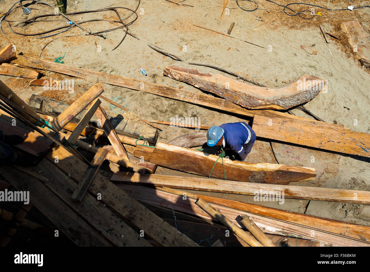 An Ecuadorian shipbuilding worker builds a traditional wooden fishing vessel in an artisanal shipyard in Manta, - Stock Image