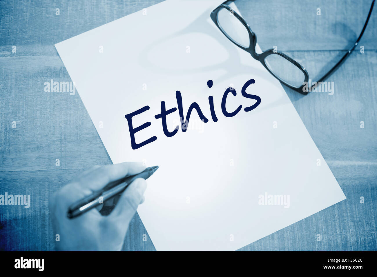 Ethics against left hand writing on white page on working desk - Stock Image