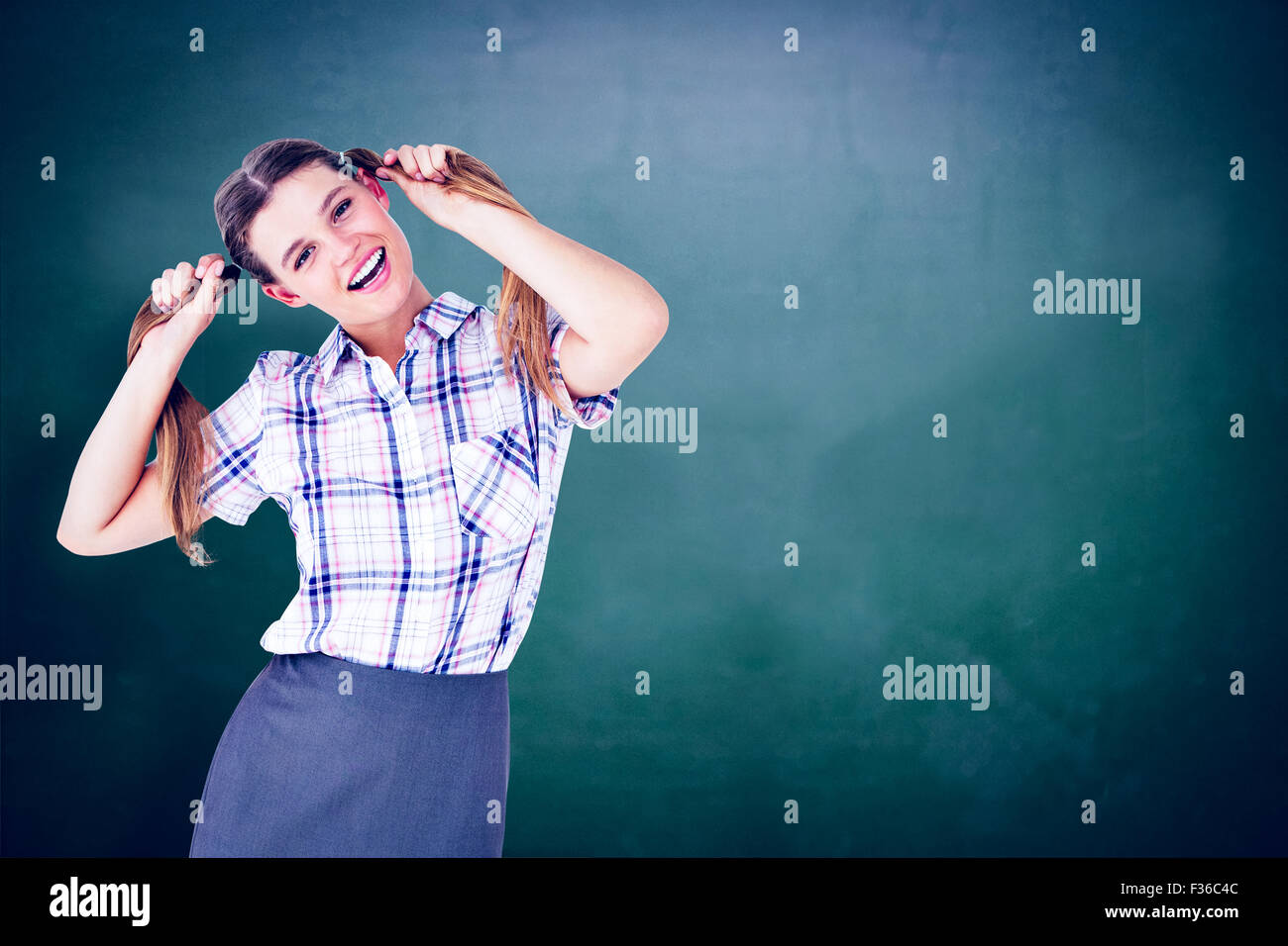 Composite image of geeky hipster holding her pigtails - Stock Image