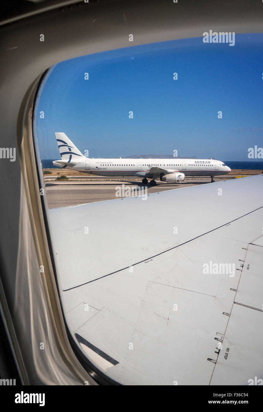An aircraft of the airline Aegean at the airport Heraklion in Crete. View from the cabin of another airliner. - Stock Image