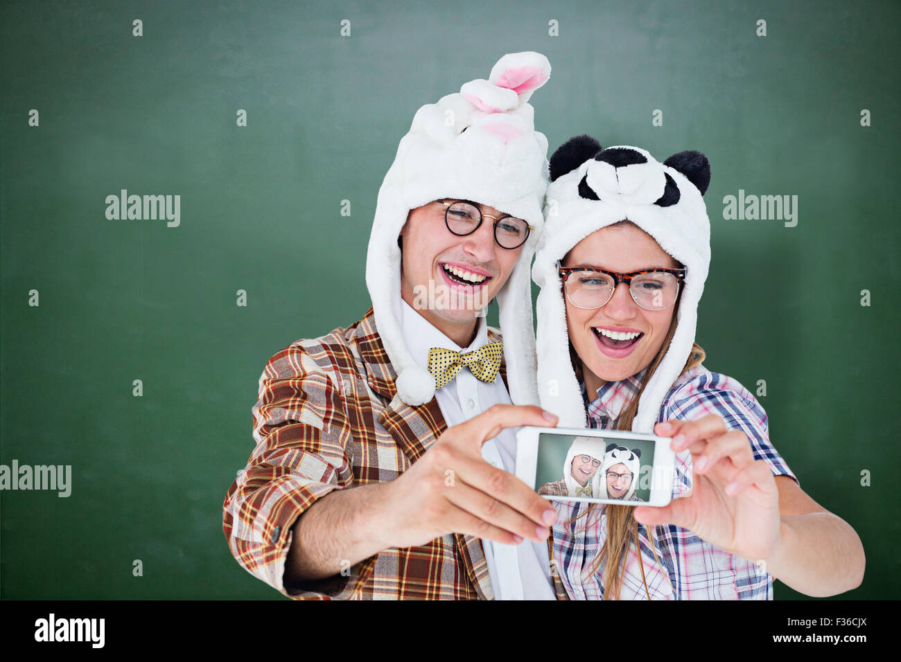 Composite image of geeky hipster couple taking selfie with smart phone - Stock Image