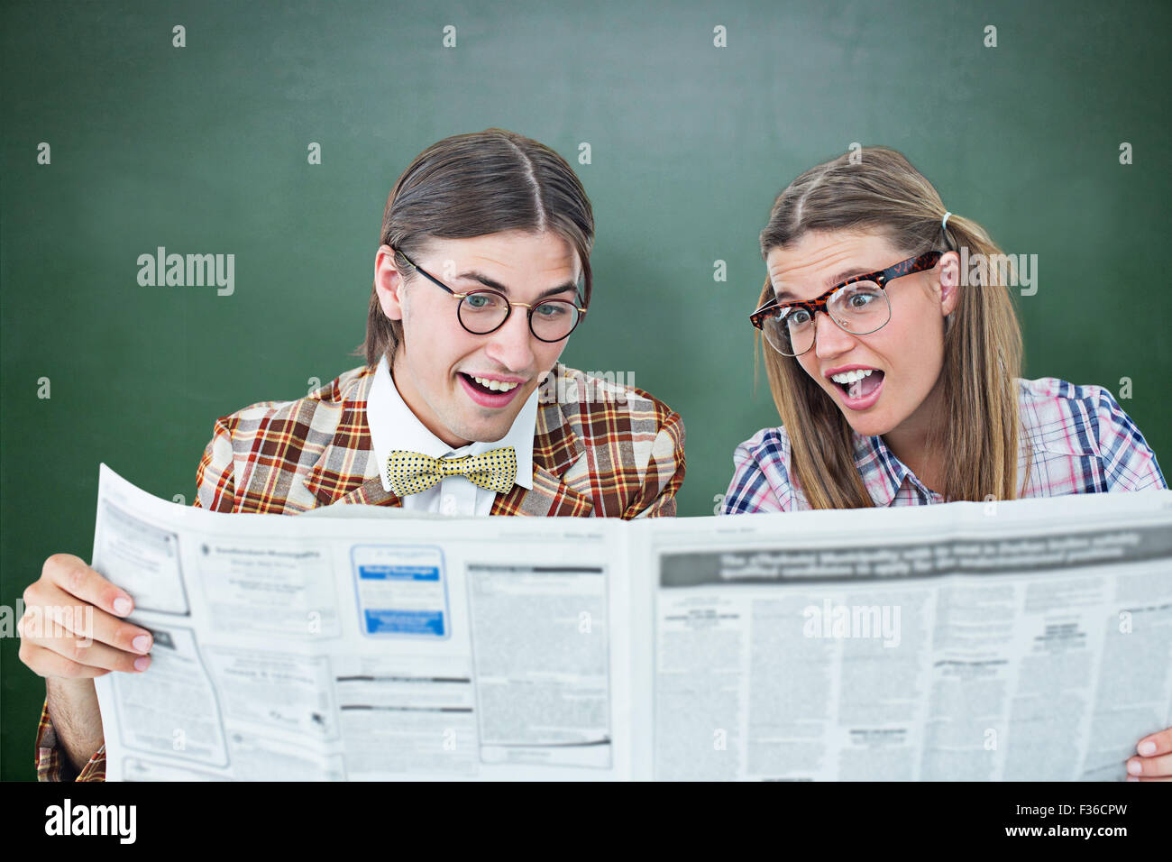 Composite image of geeky hipsters reading the newspaper - Stock Image