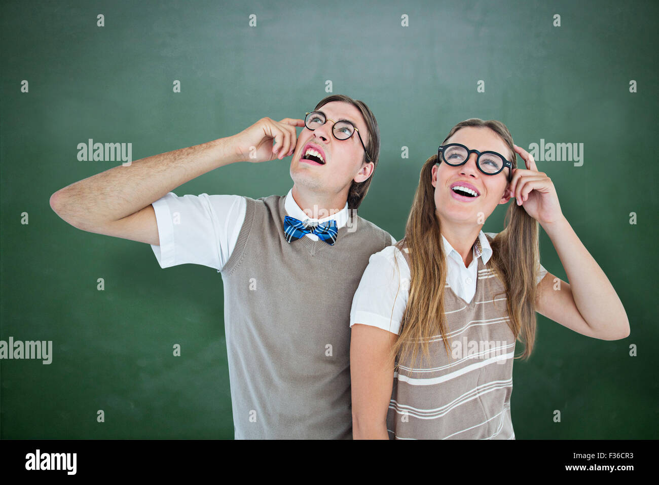 Composite image of geeky hipsters looking confused - Stock Image