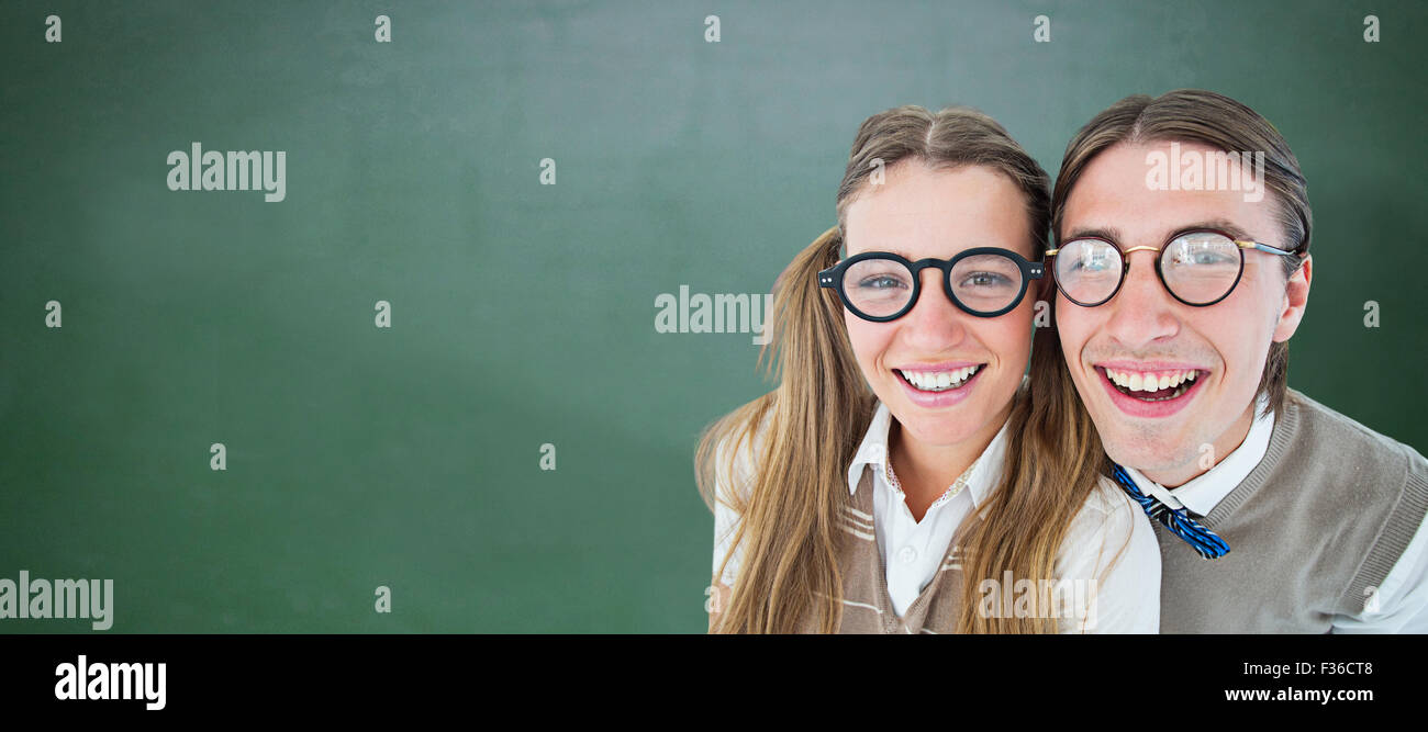 Composite image of geeky hipsters smiling at camera - Stock Image