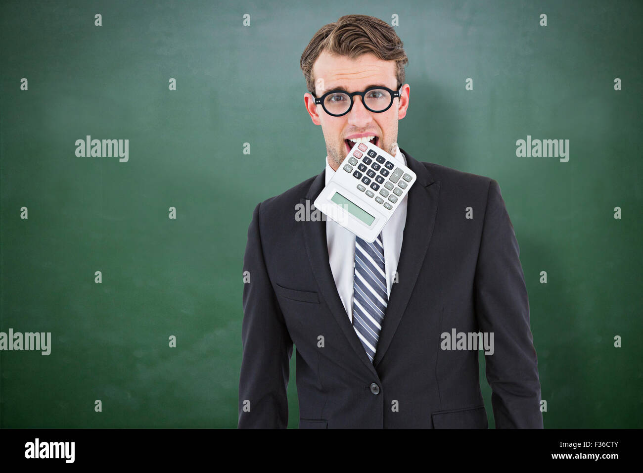 Composite image of geeky businessman biting calculator - Stock Image