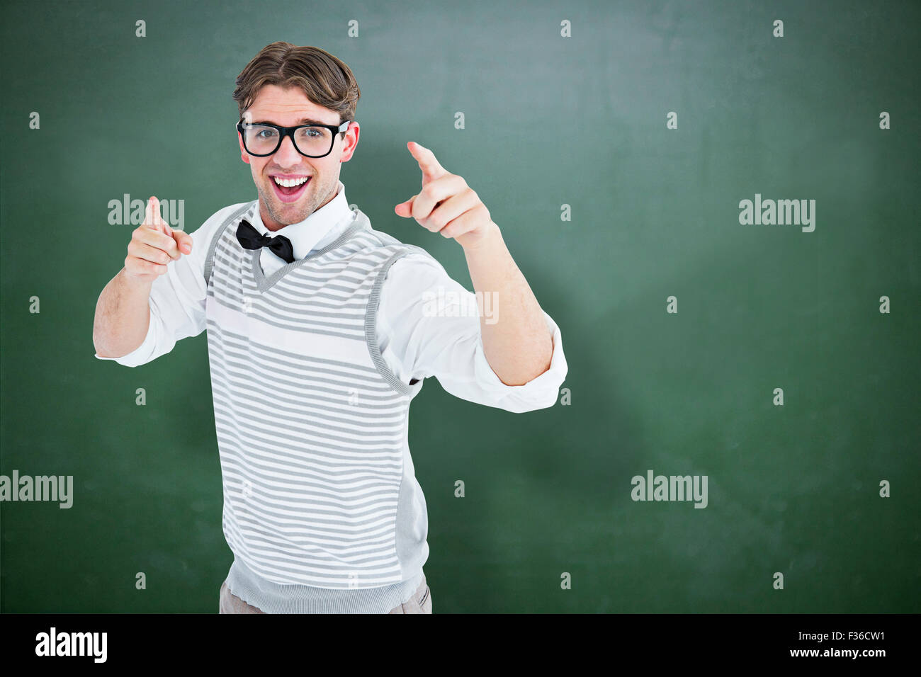 Composite image of geeky hipster in sweater vest dancing - Stock Image