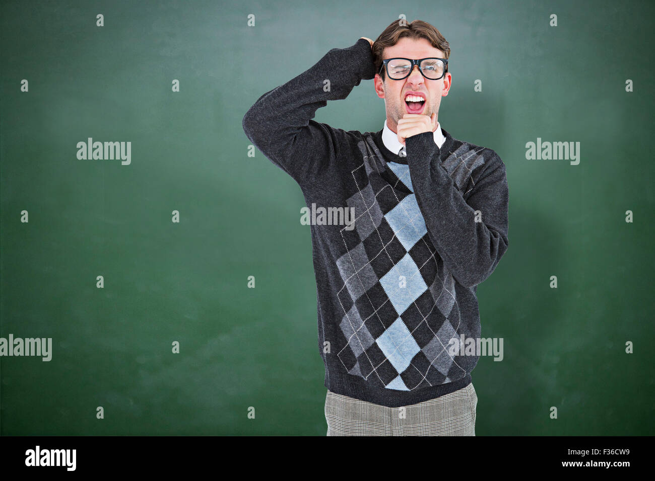 Composite image of geeky hipster frowning at camera - Stock Image