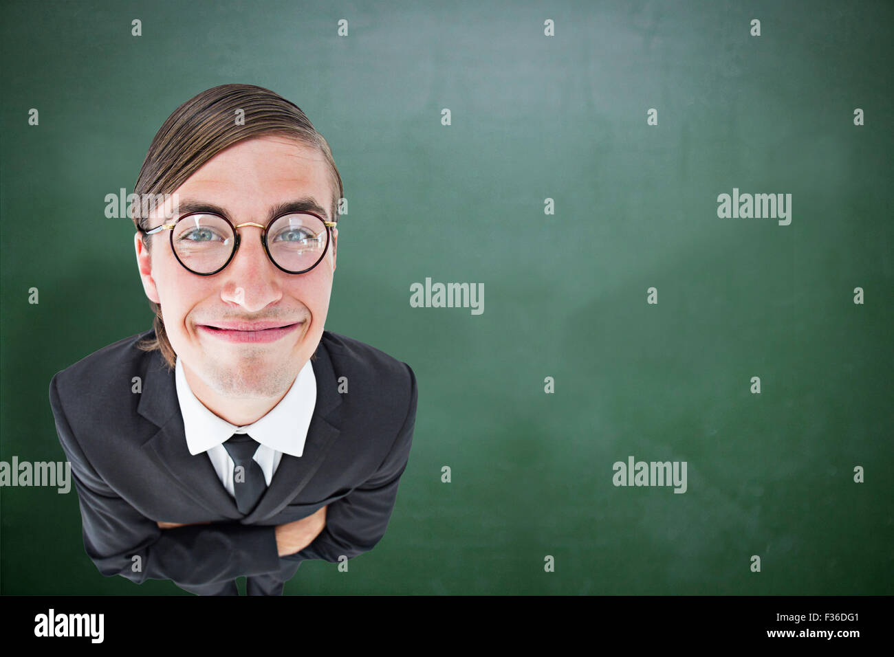 Composite image of geeky businessman smiling at camera - Stock Image