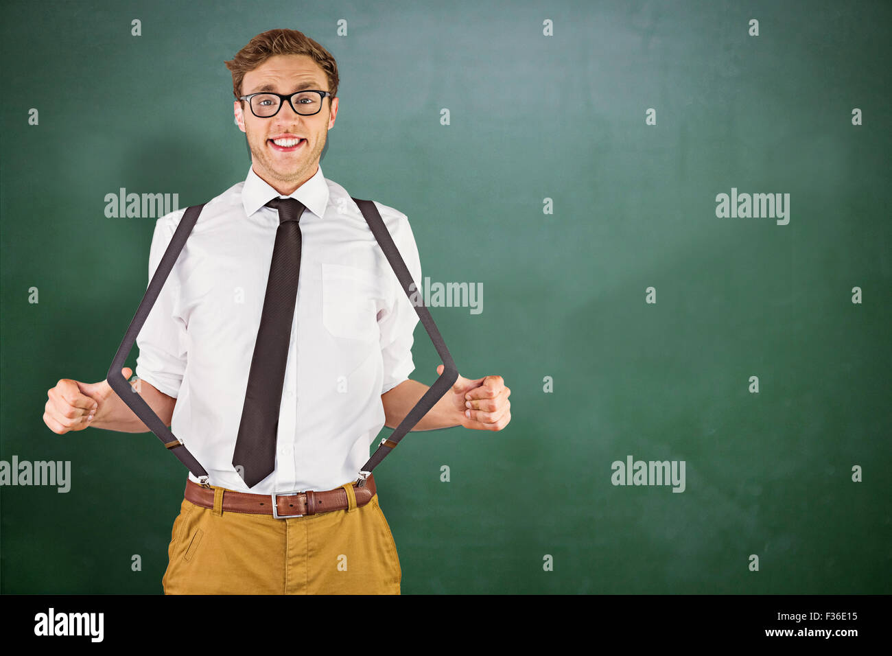 Composite image of geeky businessman pulling his suspenders - Stock Image