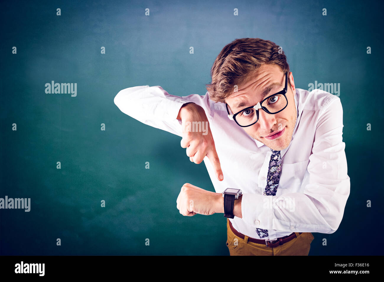 Composite image of geeky businessman pointing to watch - Stock Image