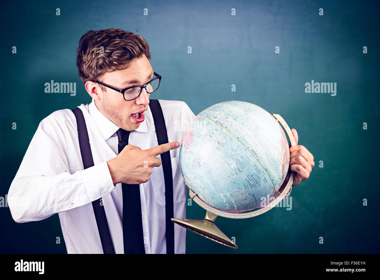 Composite image of geeky businessman pointing to globe - Stock Image