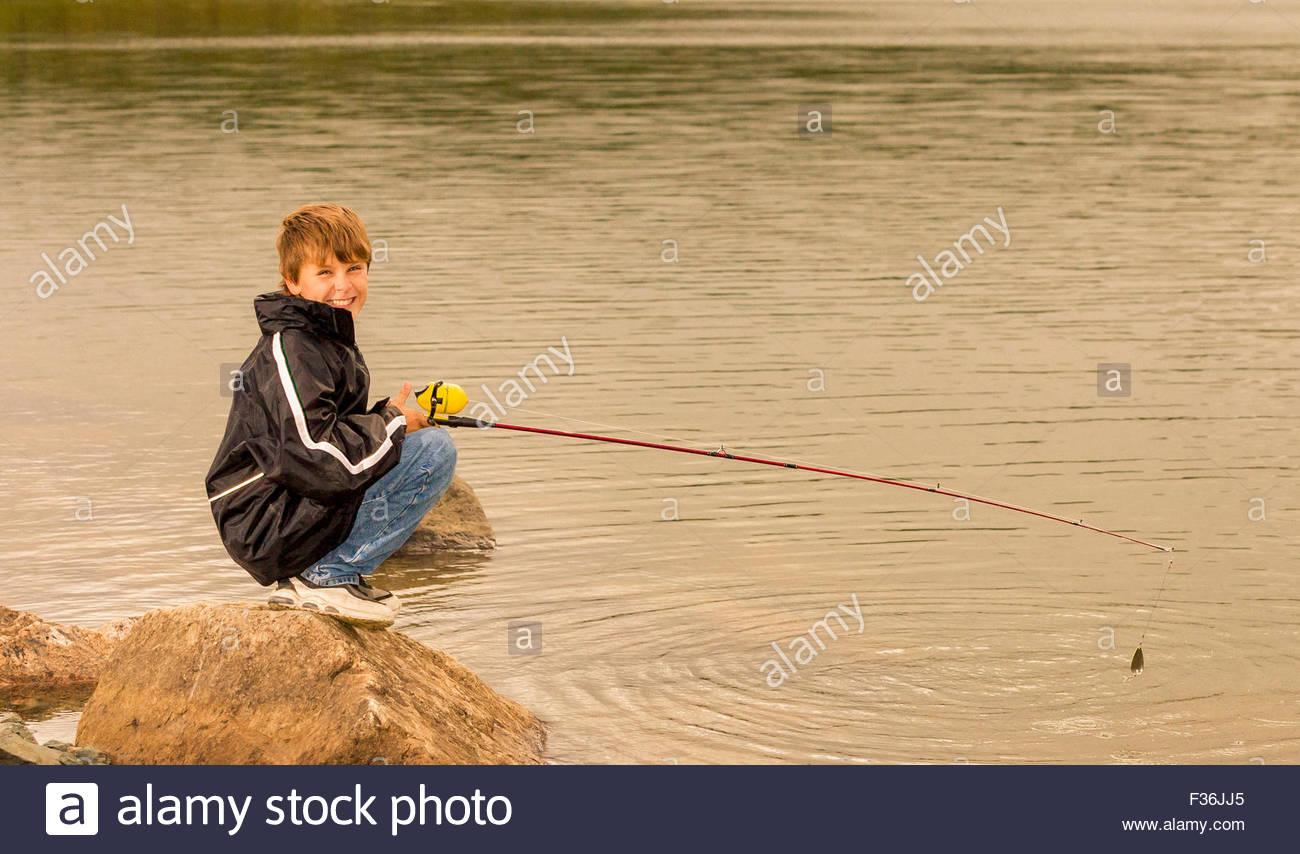 Boy fishing in northern Lake near Yellowknife, Northwest Territories. - Stock Image