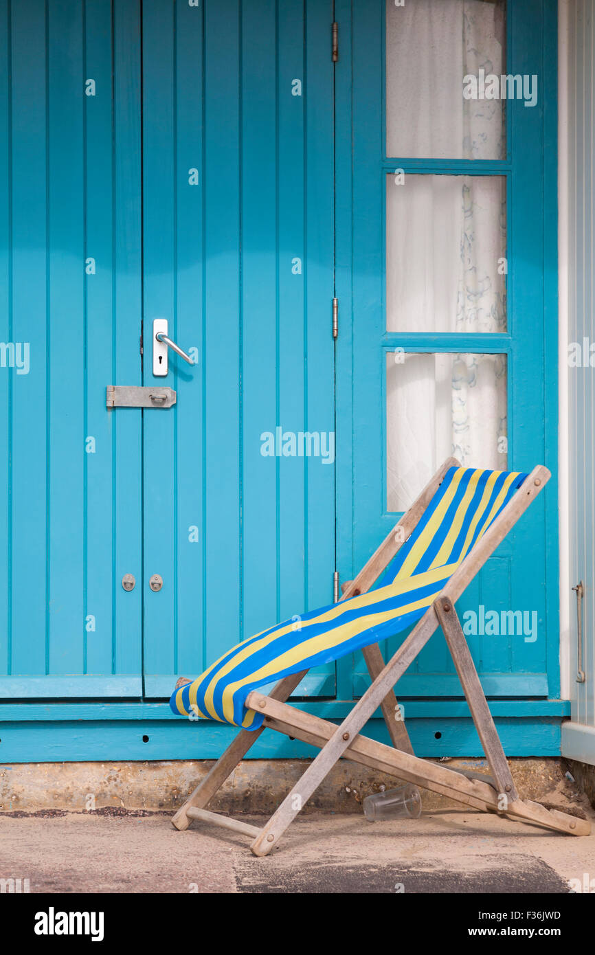 empty deckchair outside beach hut at Bournemouth in September - Stock Image