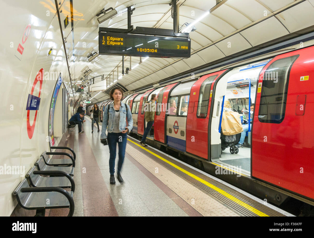 Commuters after getting off a stationary tube train at a London underground station platform London England UK Gb - Stock Image