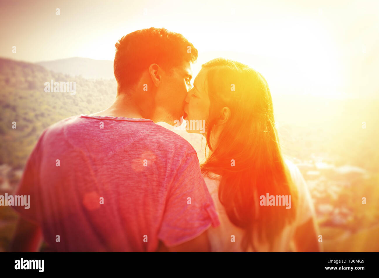 Young, kissing couple in the sun - Stock Image