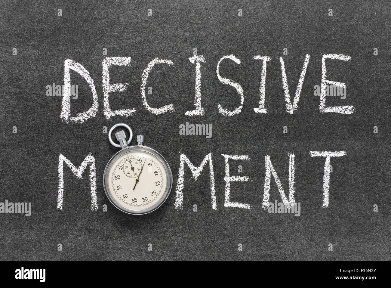 decisive moment phrase handwritten on chalkboard with vintage precise stopwatch used instead of O - Stock Image