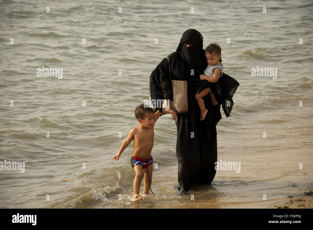 Muslim mother and her two children walking in the Red Sea of the Corniche in Jeddah, Saudi Arabia - Stock Image