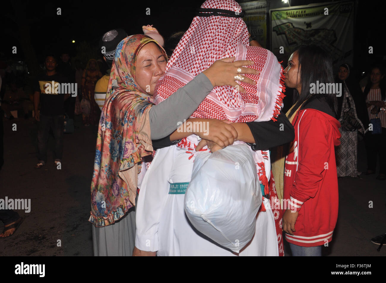 Makassar, Indonesia. 30th Sep, 2015. Indonesian hajj pilgrim gets emotional welcome from his family at Sudiang Hajj - Stock Image