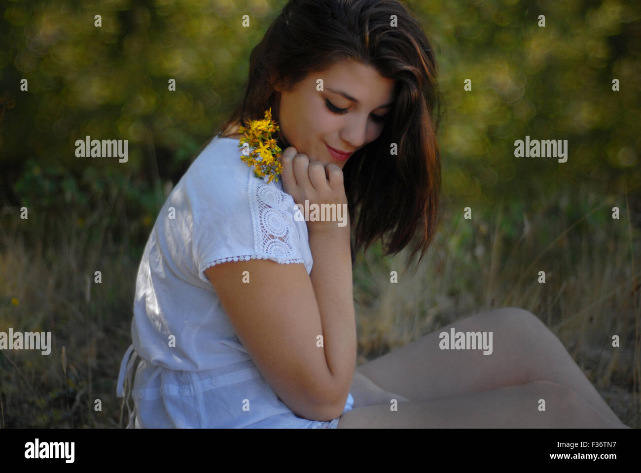 beauty girl looking down with yellow flowers in her hands in a white dress - Stock Image