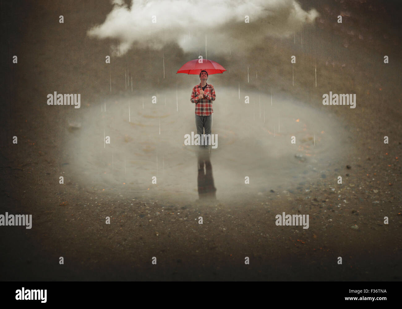 Miniature boy smiling standing in a puddle with a red umbrella with a big cloud - Stock Image