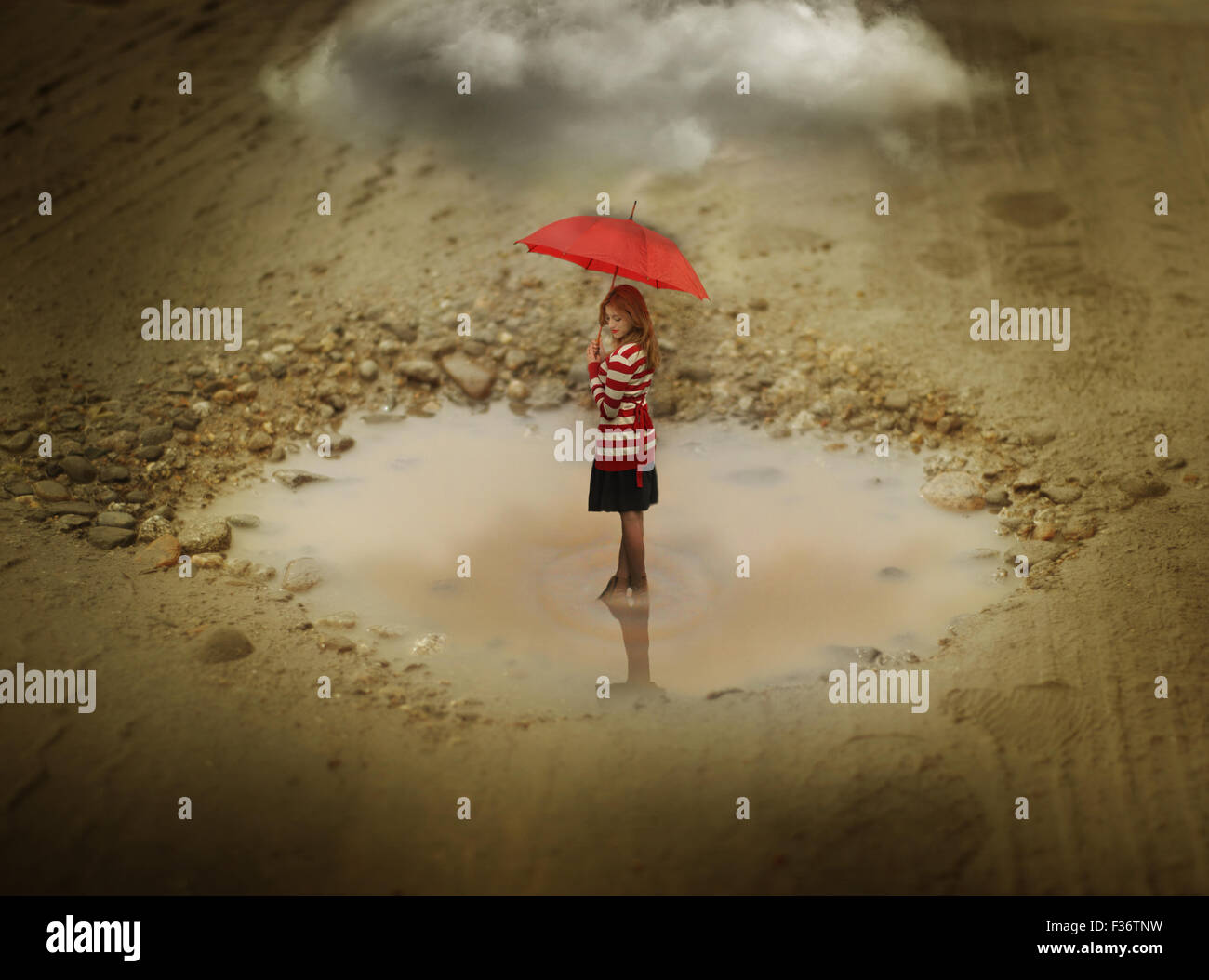 Miniature girl looking down standing in a puddle with a red umbrella with a big cloud - Stock Image