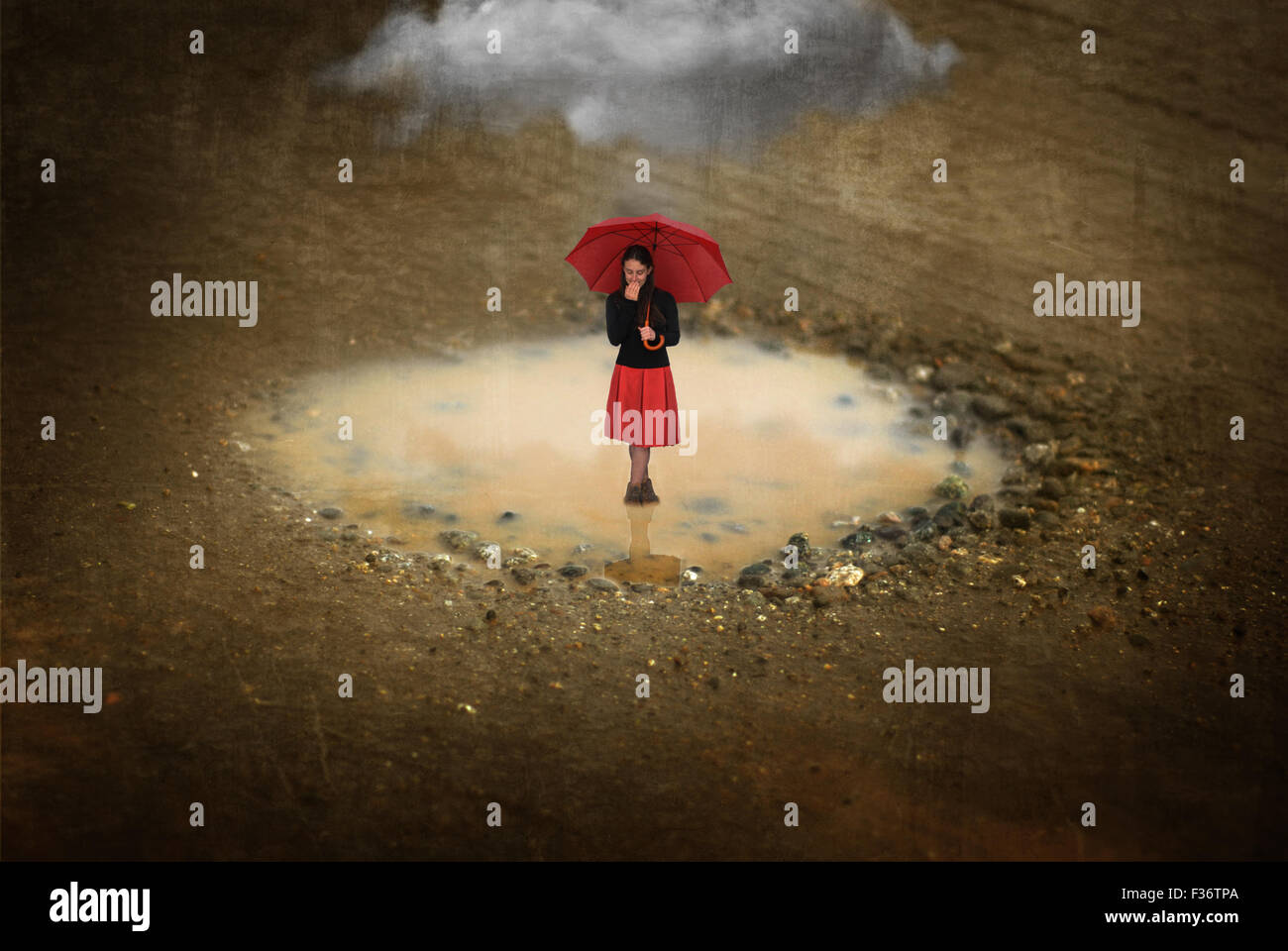 Miniature girl standing in a puddle with a red umbrella with a big cloud - Stock Image