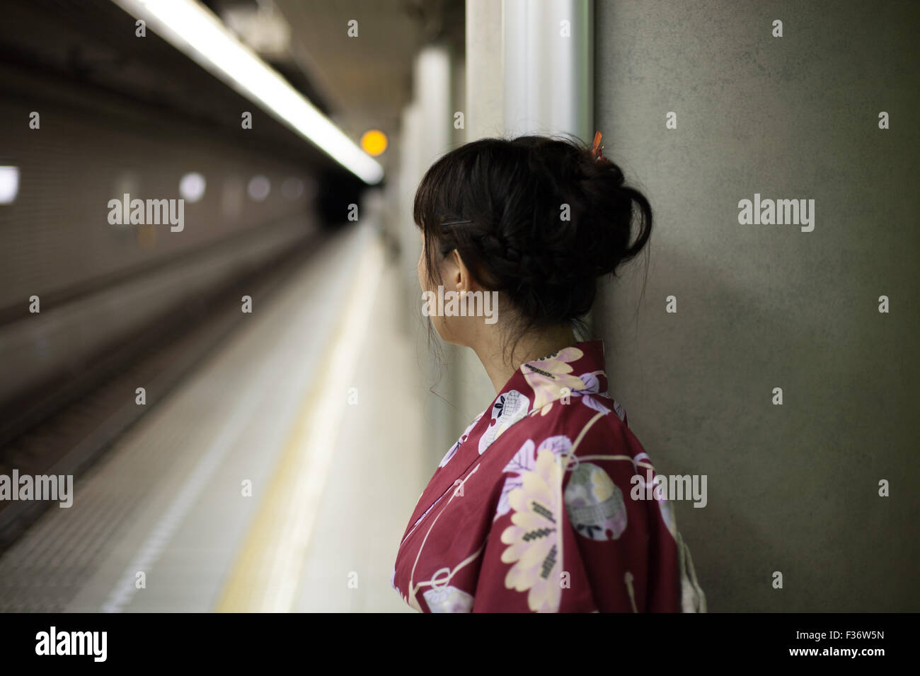 Girl in kimono waiting on subway platform Stock Photo