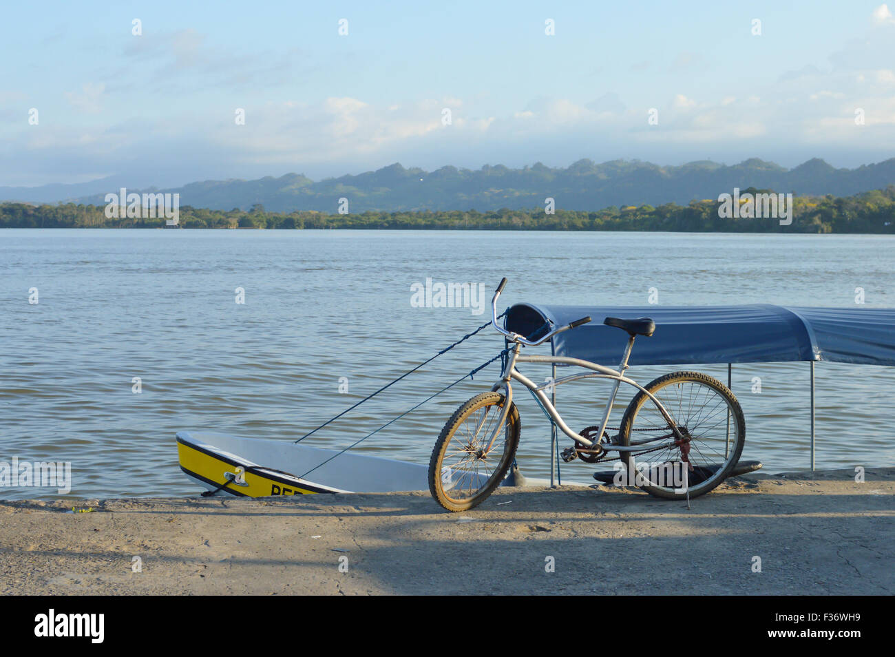 Bicycle and a boat at the pier of little Garifuna town of Livingston with the river Rio Dulce on the background, - Stock Image
