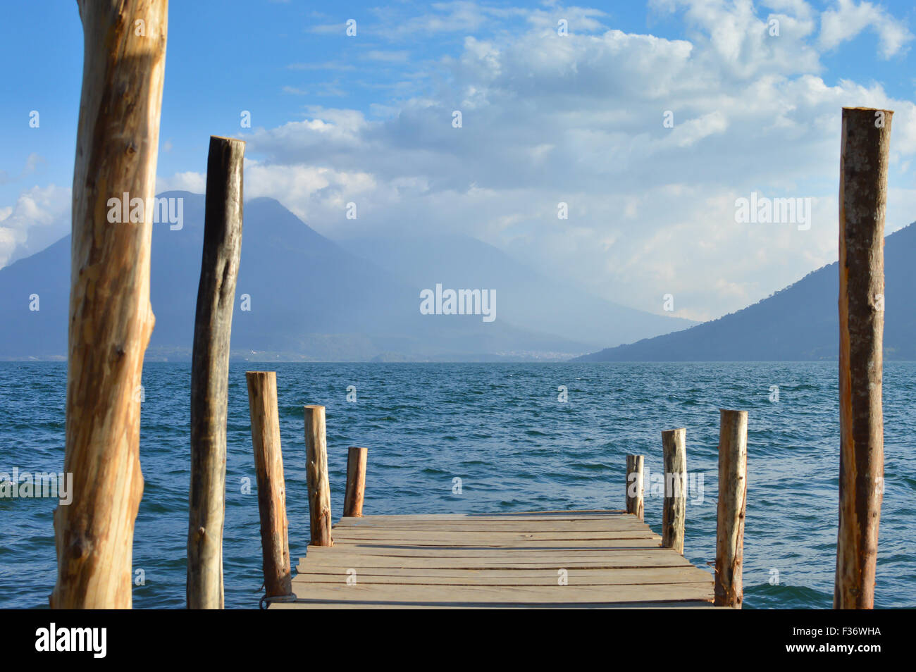 Boat dock at a small village of San Marcos on the Lake Atitlan in Guatemala with the volcanoes on the background - Stock Image