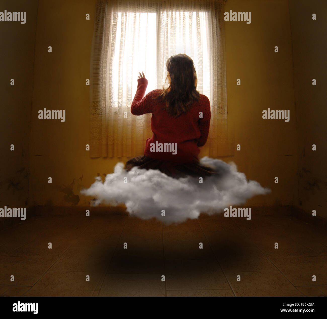 Girl levitating in a cloud inside an empty room surreal dreams - Stock Image