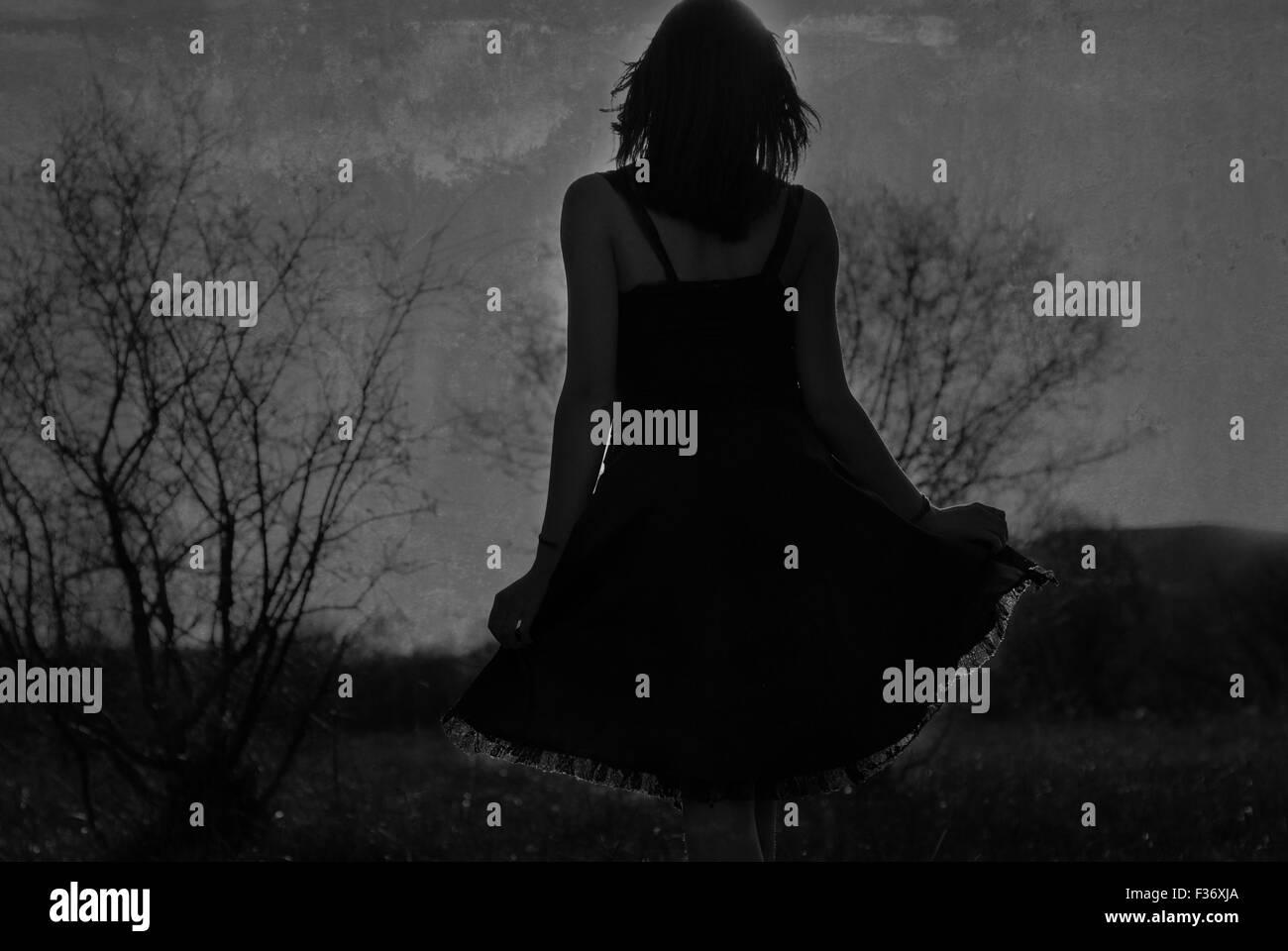 girl in a dark dress backlighting - Stock Image