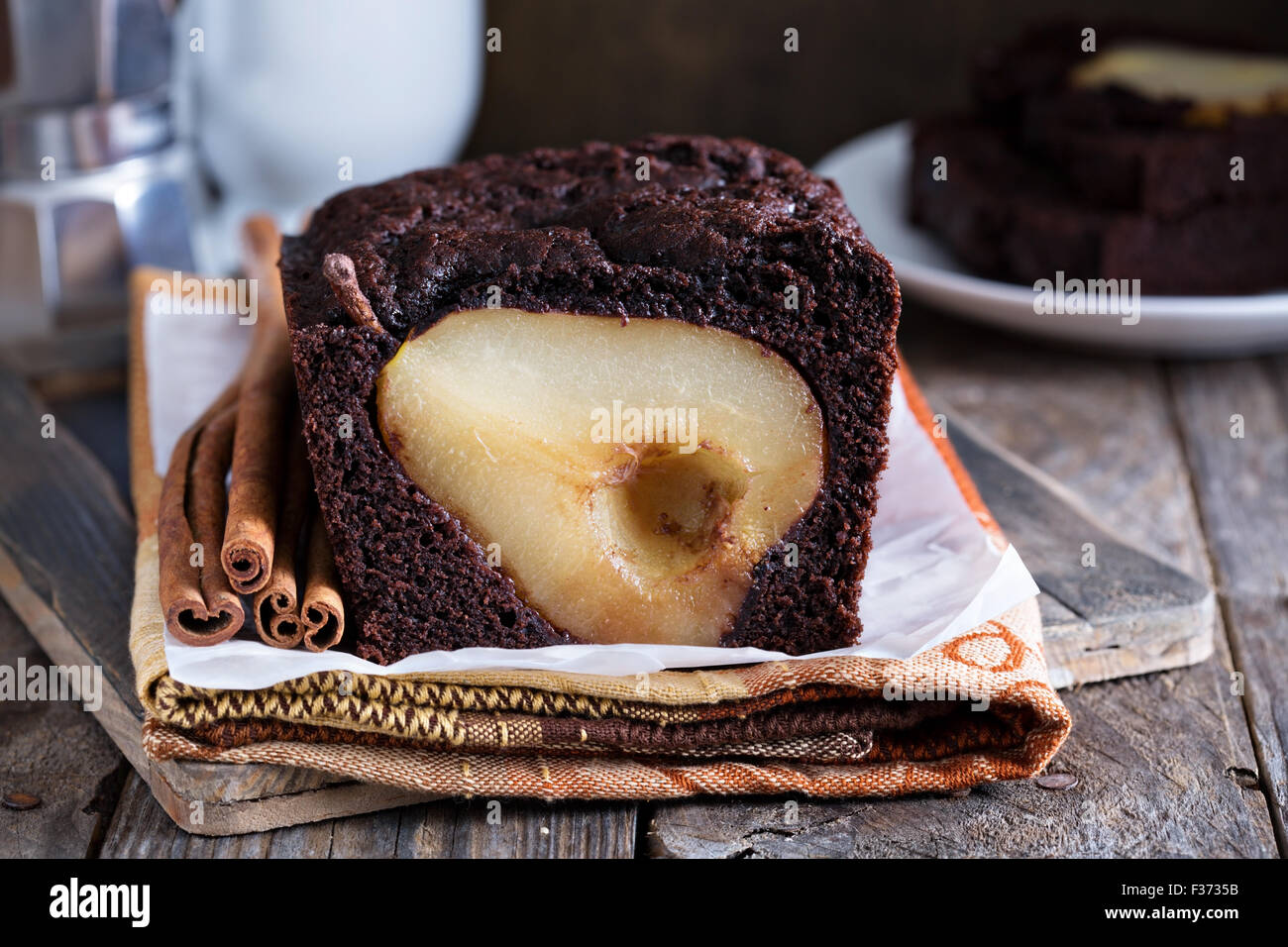 Chocolate loaf cake with whole pears baked inside - Stock Image