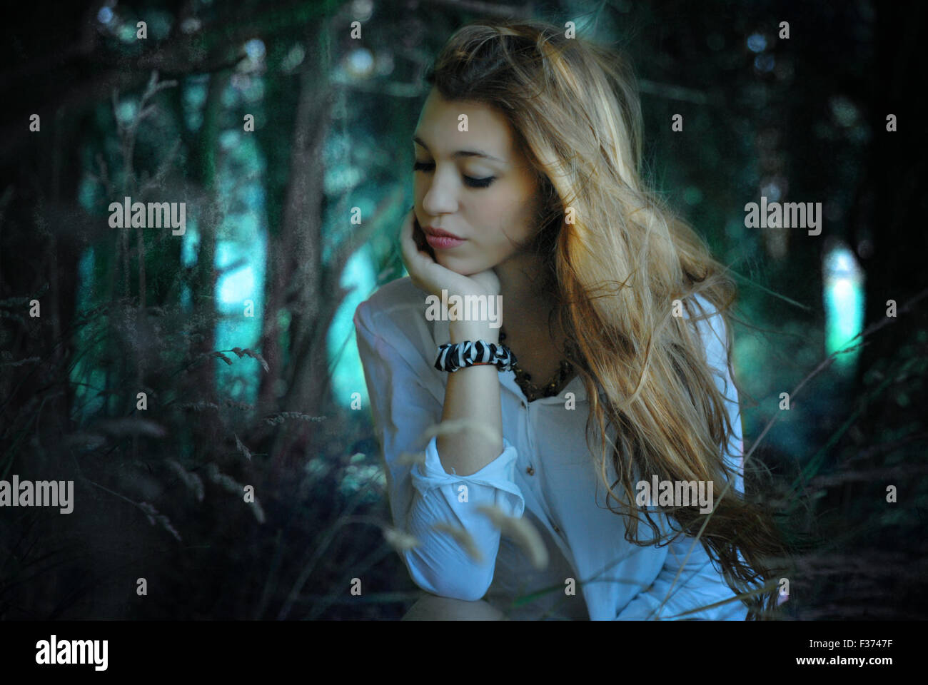 ginger girl touching her face looking down in the forest - Stock Image