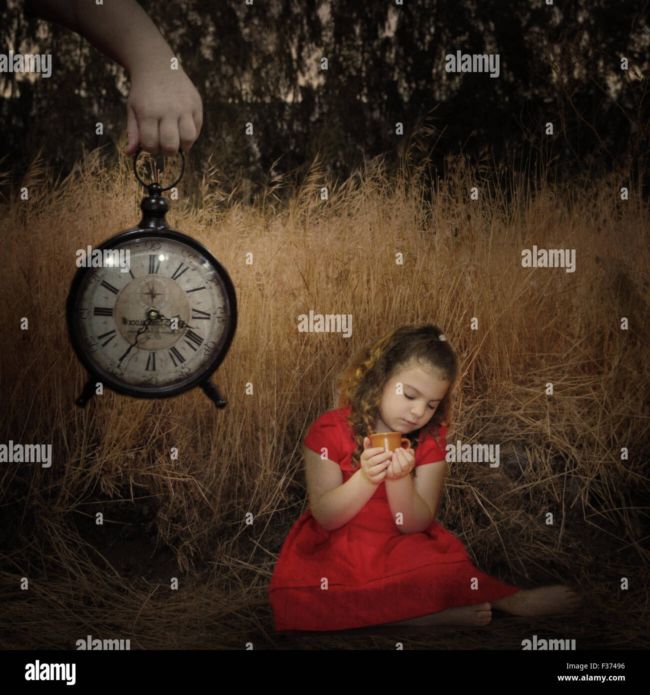girl in the fields with big hand and a clock surreal - Stock Image
