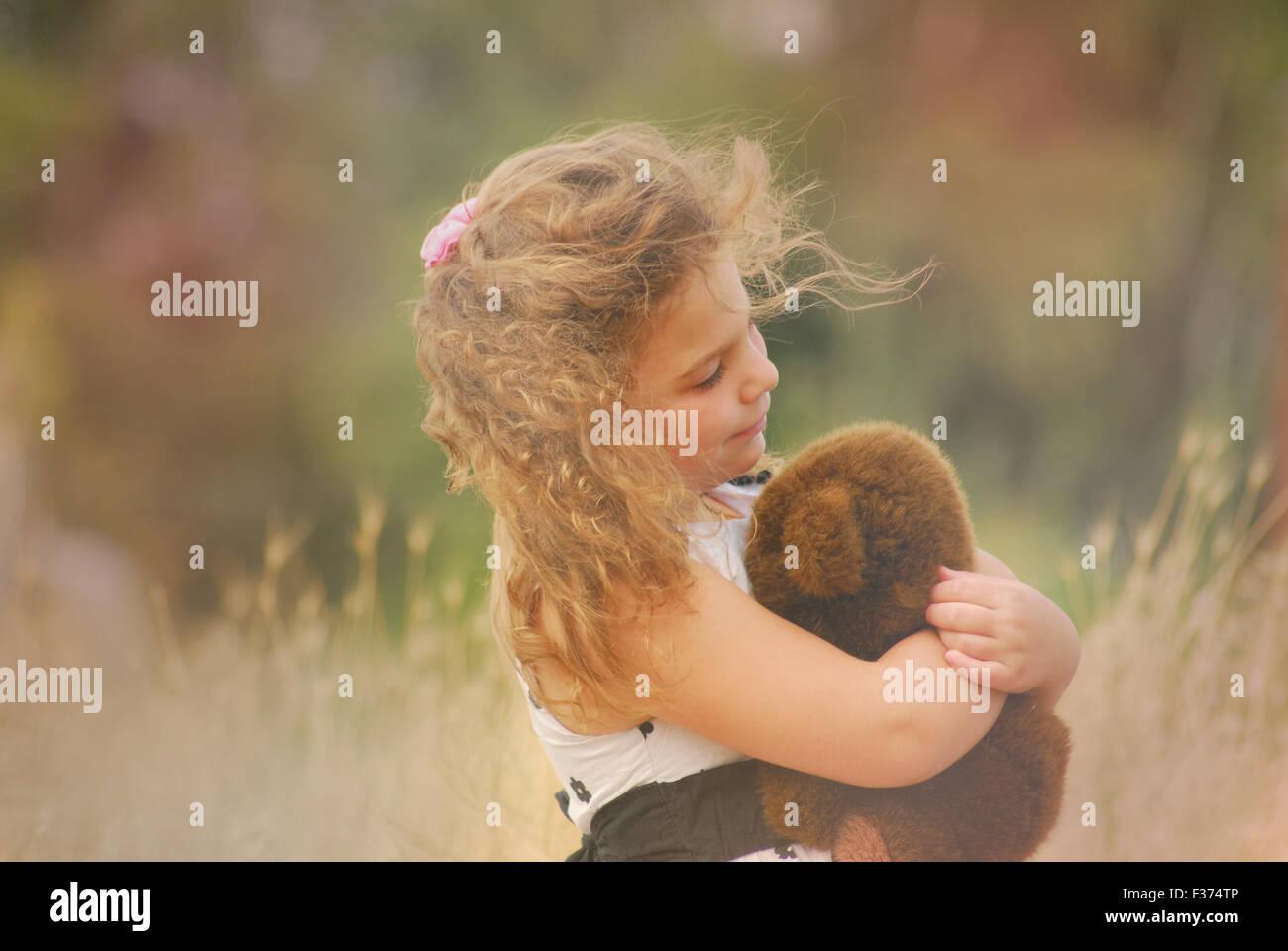 Little girl embracing her teddy bear - Stock Image