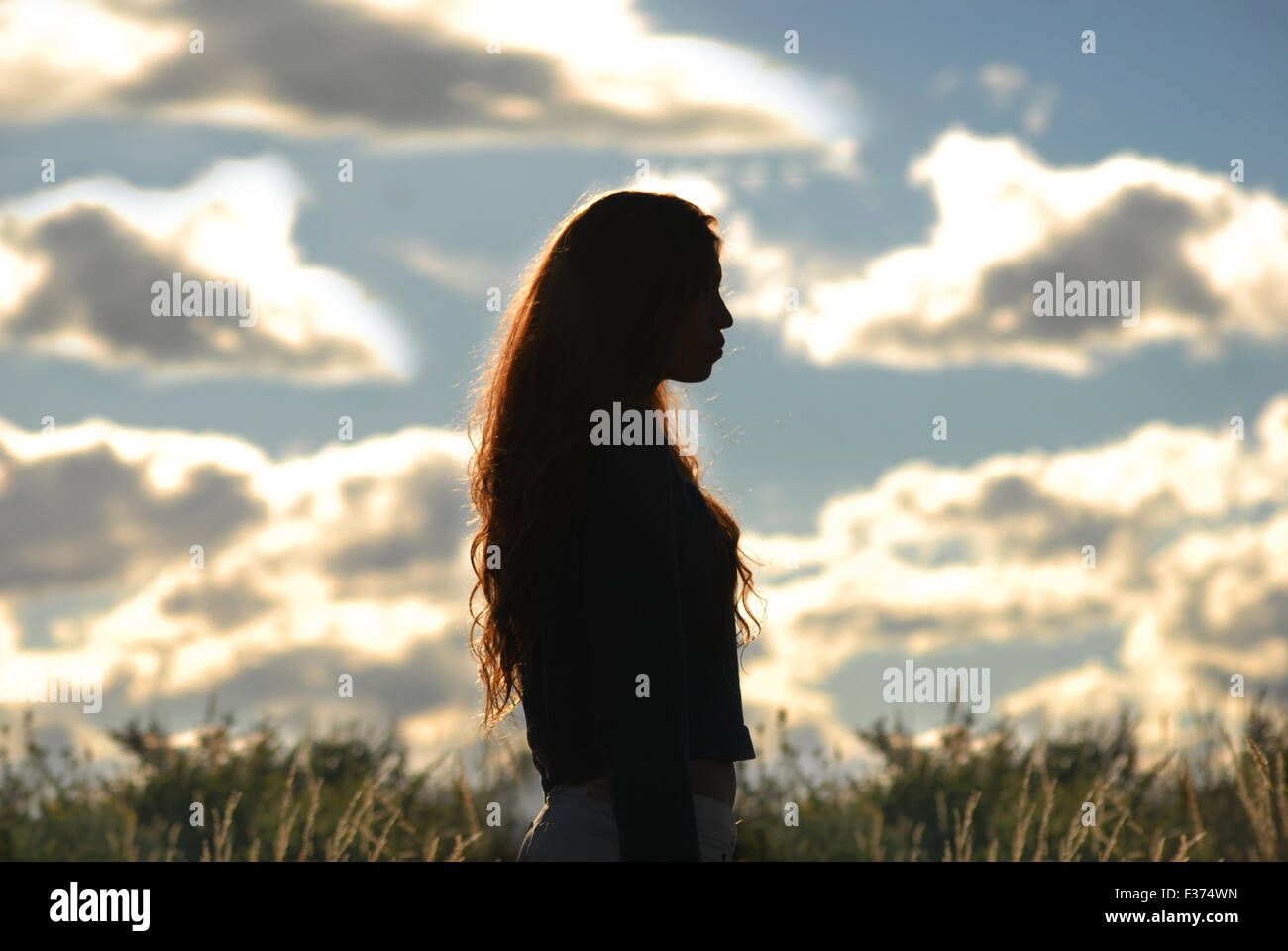 Shadow of a girl with a cloudy sky behind - Stock Image