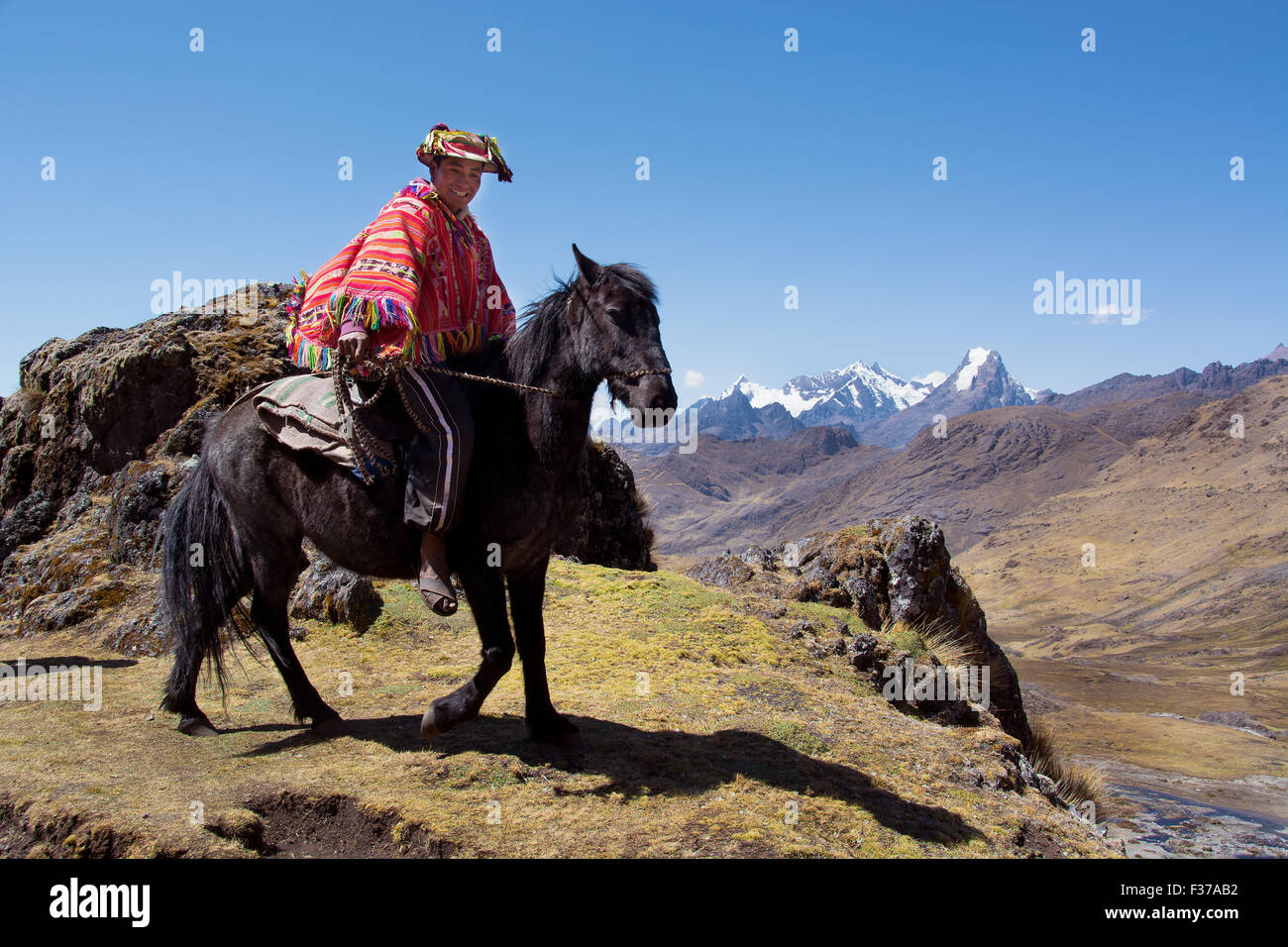 Indio mountain guide with colorful poncho riding on horseback, in the mountains, Andes, Cusco Province, Peru - Stock Image
