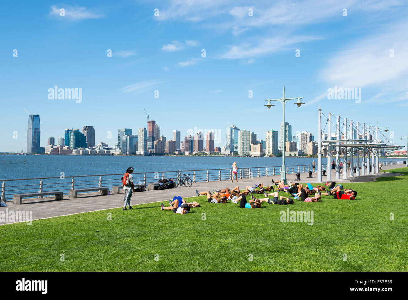 NEW YORK CITY, USA - AUGUST 29, 2015: Personal trainer leads group boot camp fitness class on the grass near the - Stock Image