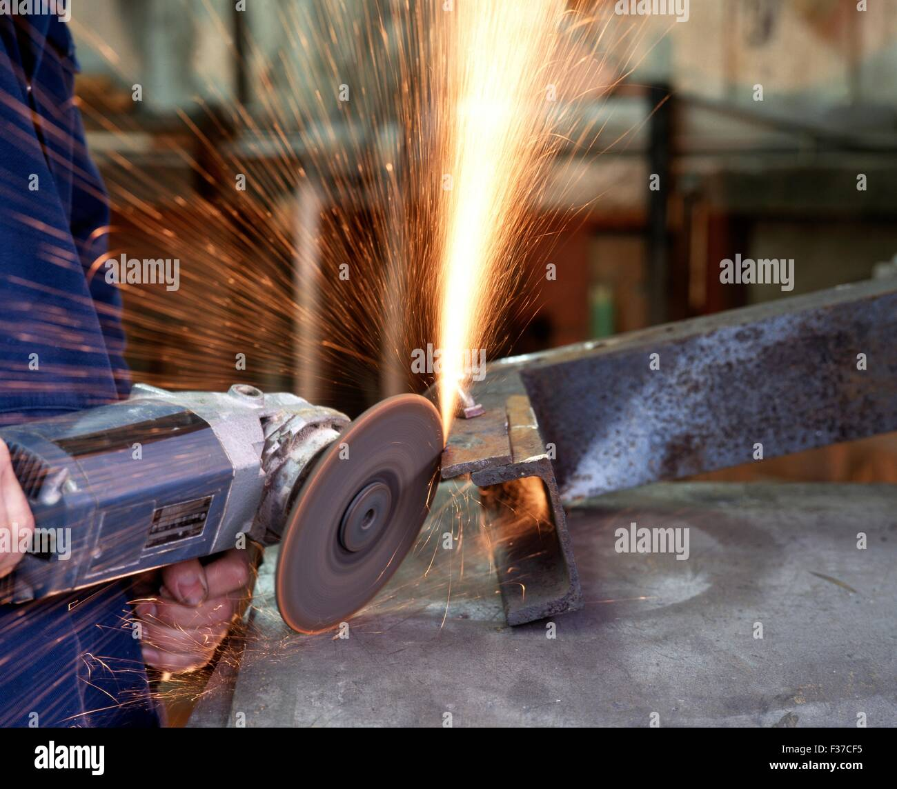 Man using an angle grinder to cut and shape mild steel, Aldridge, West Midlands, UK, Western Europe. - Stock Image