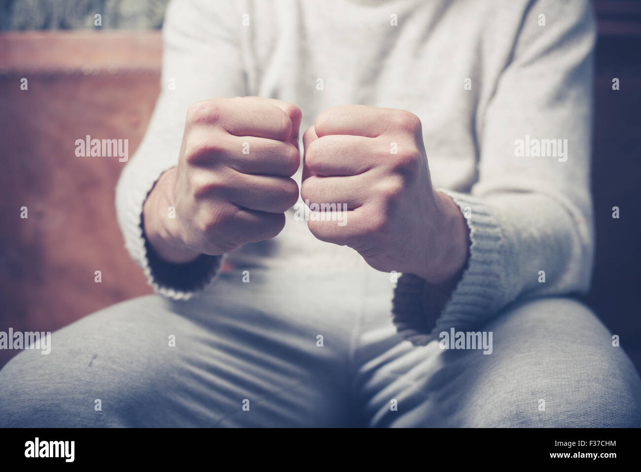 Young man is sitting on a sofa with his fists clenched - Stock Image