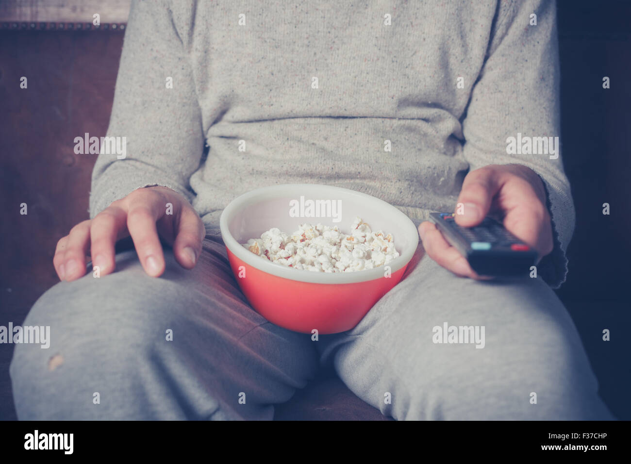 Young man is sitting on a sofa and eating popcorn while watching television - Stock Image